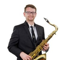 nick holding sax in suit