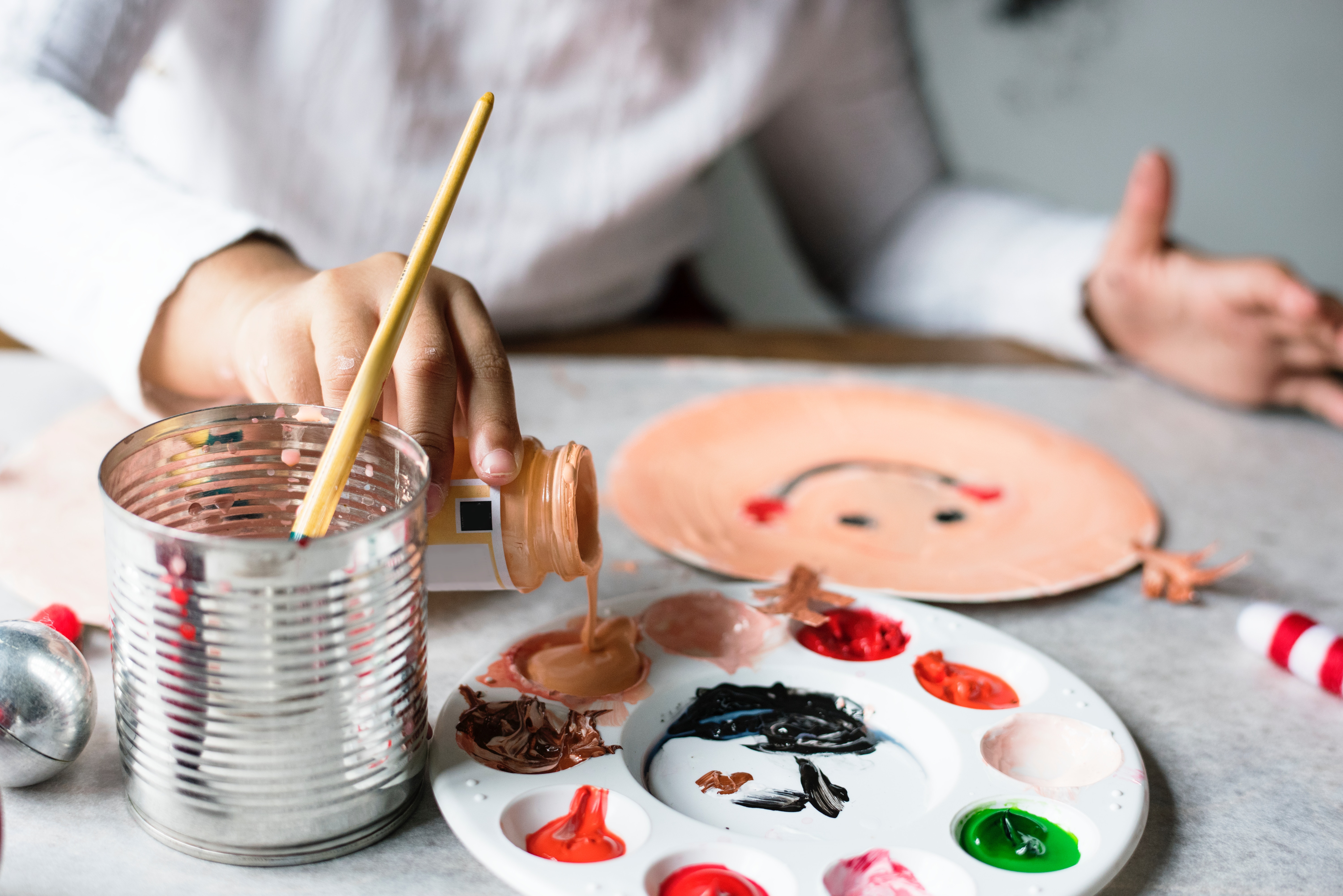 child pouring paint in tray